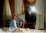 Mickey Leland with boxing champion Sugar Ray Leonard ; Jim Wright ; Unknown others ; at dinner in the Capitol